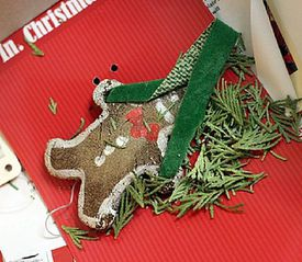 A gingerbread cookie in a box with some evergreen sprigs and a ribbon