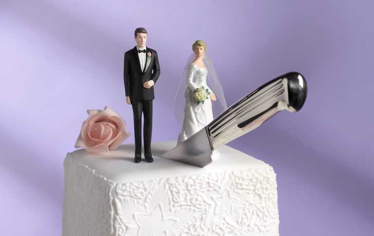 Toy couple on wedding cake with knife cutting between them