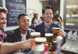 Men friends toasting beer glasses at bar