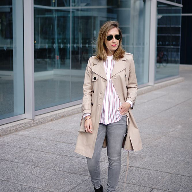 Woman in trench coat and grey jeans