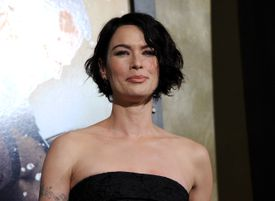 Lena Headey appears at a press event for the movie '300' wearing a black strapless dress and a short, dark hairstyle.