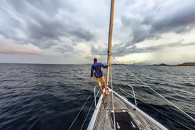 Man standing on sail boat