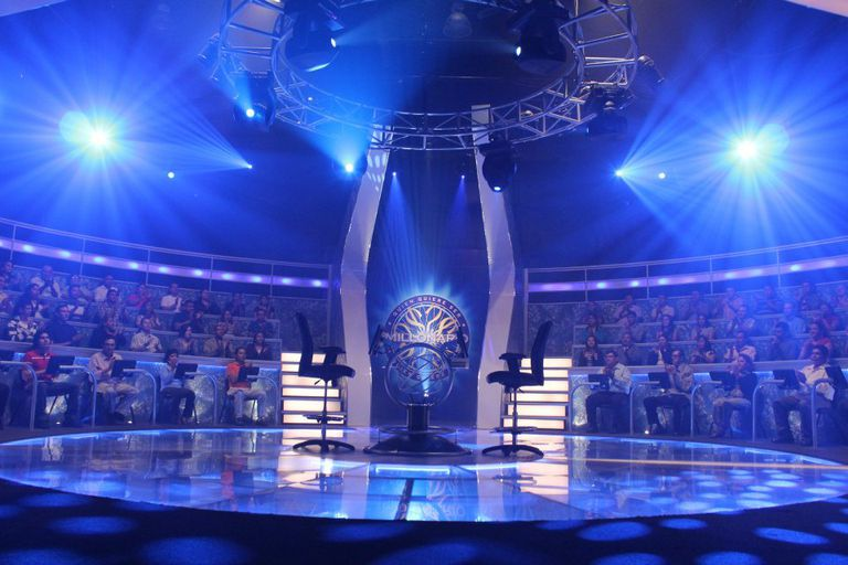 "The ""Who Wants to Be a Millionaire?"" stage with empty chairs and full audience."