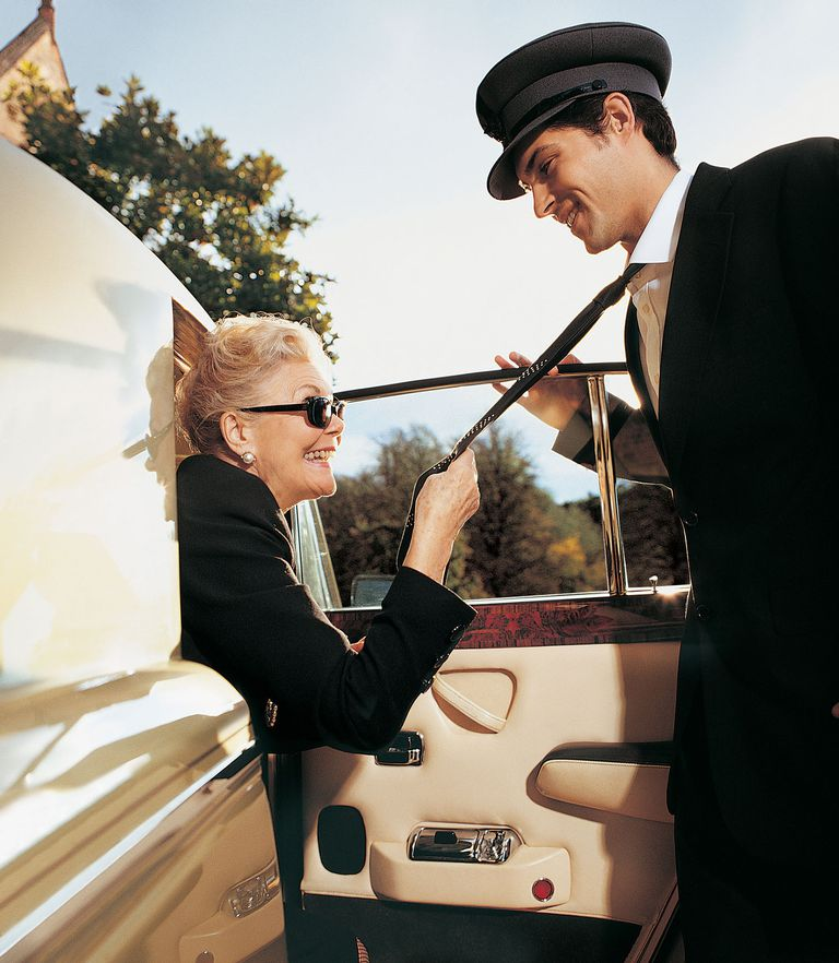 One Senior Woman Alighting From a Limousine Holding the Tie of Her Chauffeur