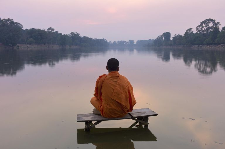 Buddhist monk at sunset looking out at a lake.
