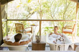 a couple bathing in side by side bathtubs