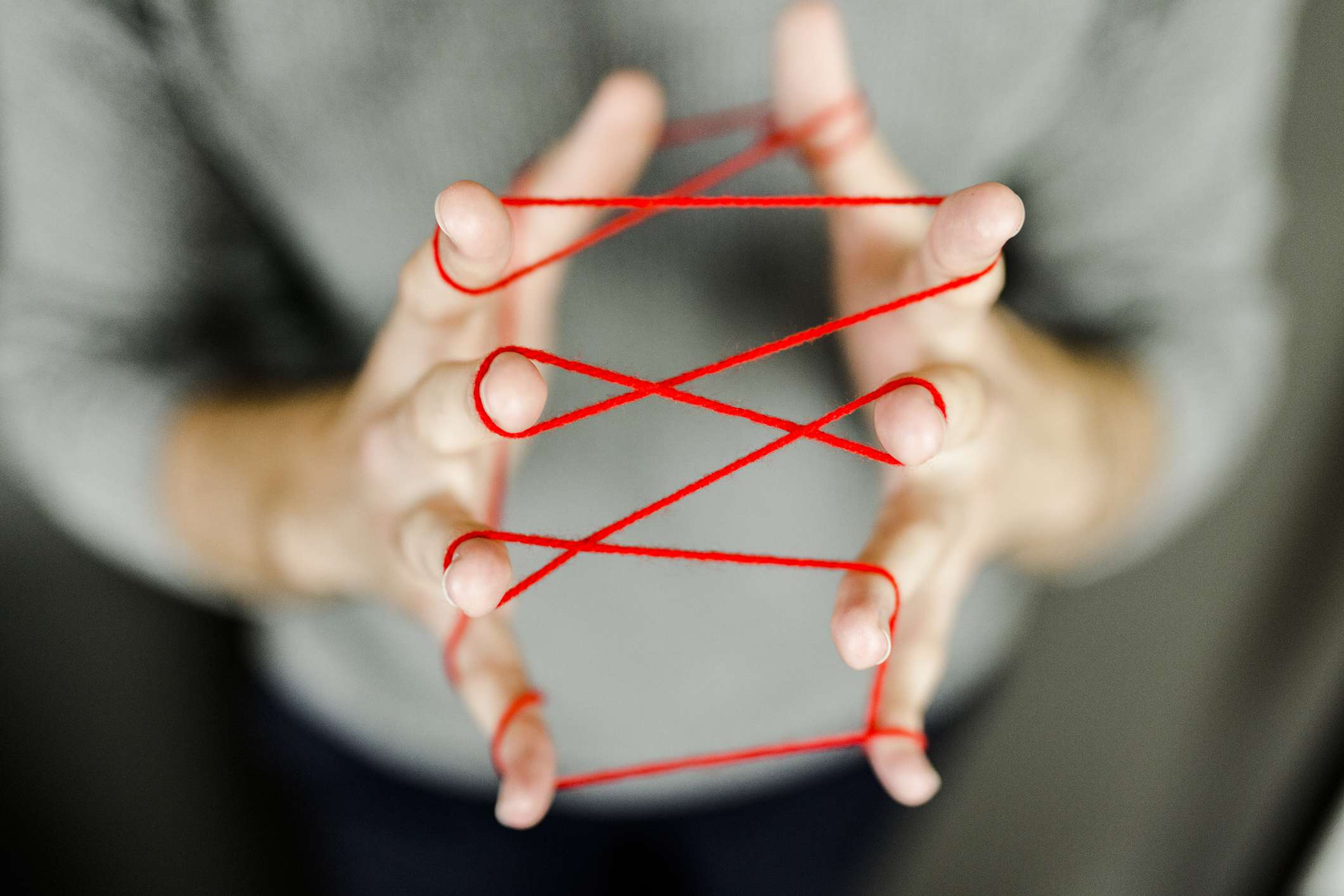 Image of a person holding thread in their fingers.
