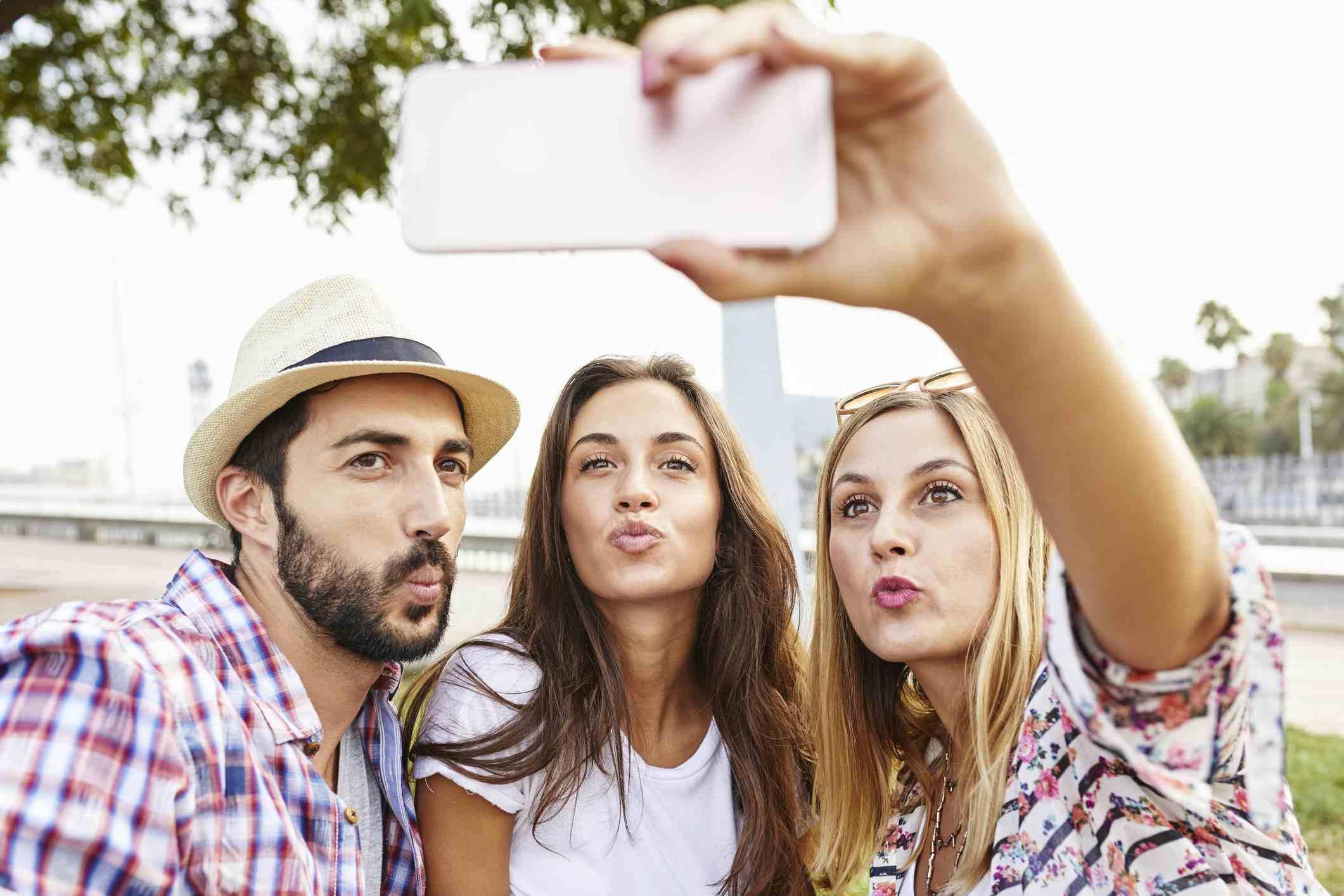 Friends outside taking a selfie.