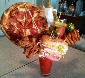 bloody mary garnished with pizza, sandwich, and more