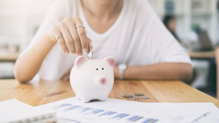 Woman dropping coin in piggy bank