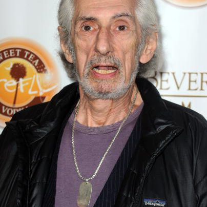 Larry Hankin with mouth open in front of promotional signs.