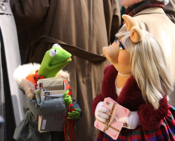 Movie still of Kermit and Miss Piggy holding letters in a crowd.