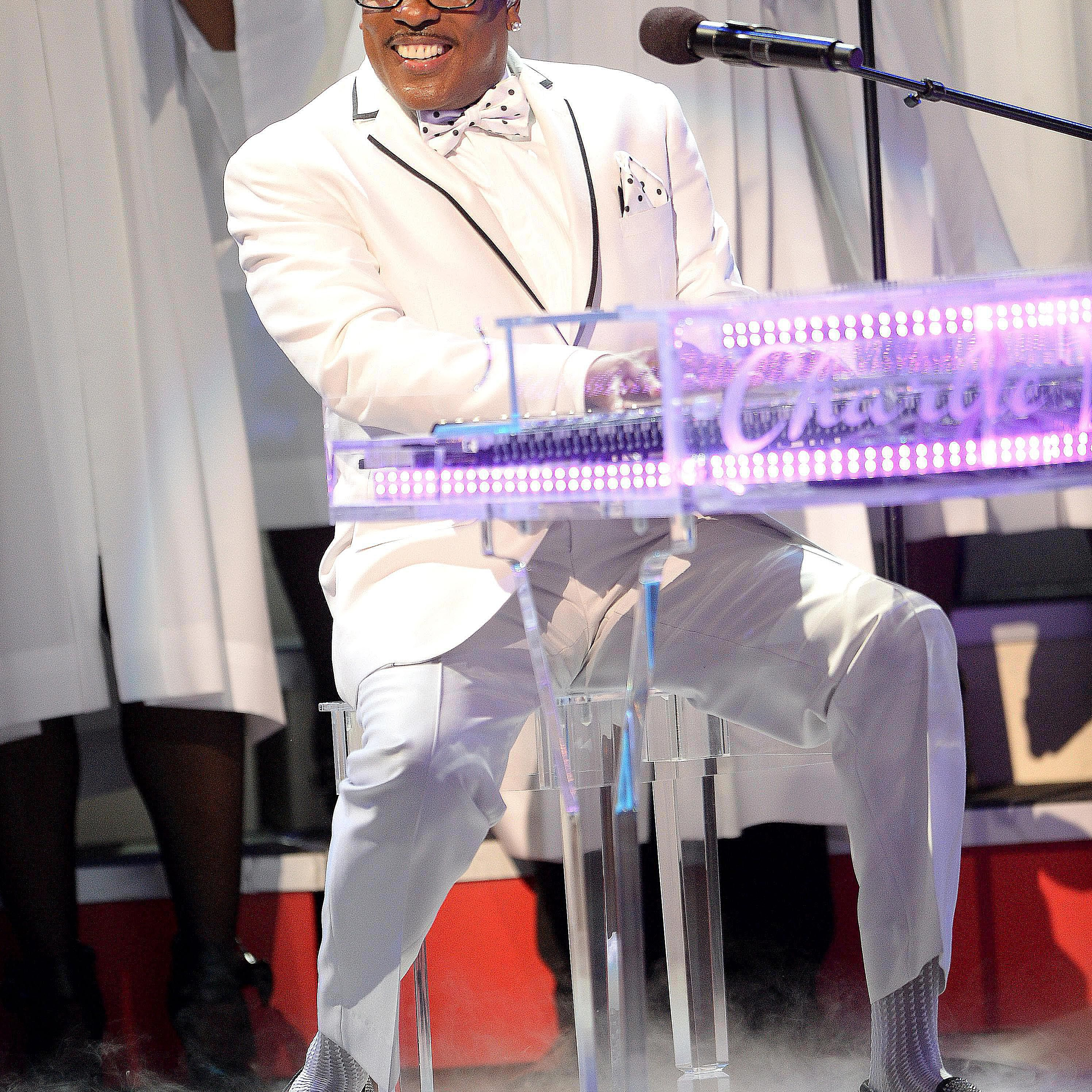 Charlie Wilson playing a clear acrylic piano