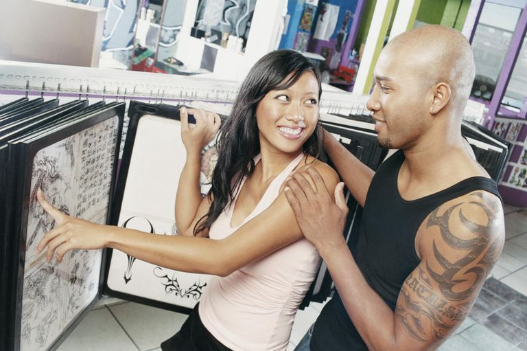 Woman in a Tattoo Parlour Showing a Tattoo Design to a Man