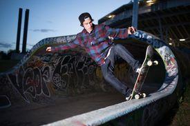 Skateboarder doing a tail stall in bowl at skatepark
