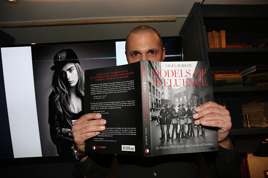 """Nigel Barker holding up his book """"Models of Influence."""""""