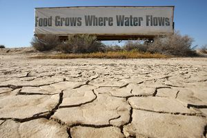 A sign on a farm trailer hangs over dry, cracked mud at the edge of a farm near Buttonwillow, California.