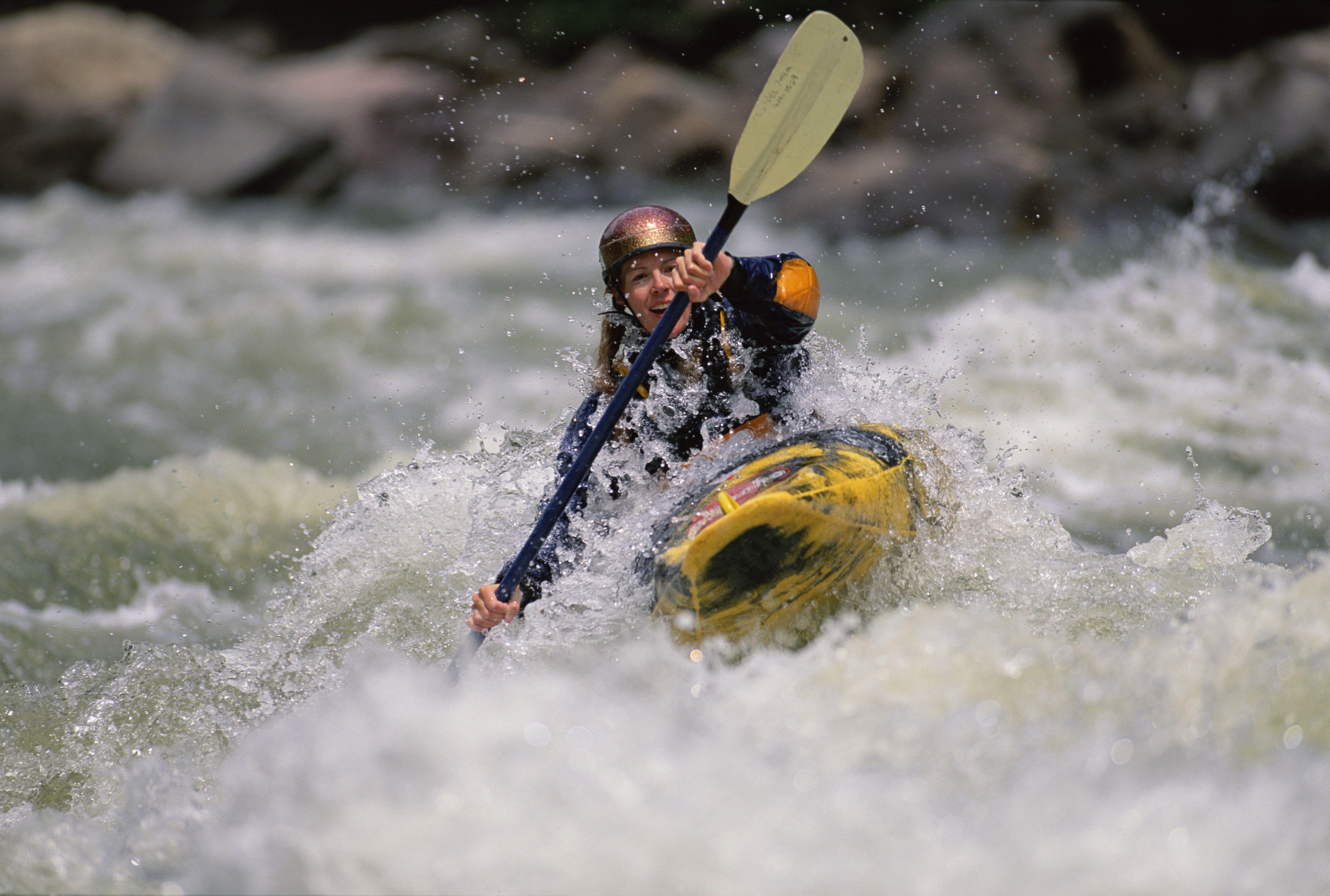 Woman whitewater kayaking