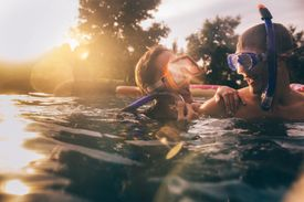 A couple swimming with snorkels and masks