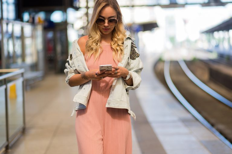 Street style woman in pink jumpsuit and jean jacket