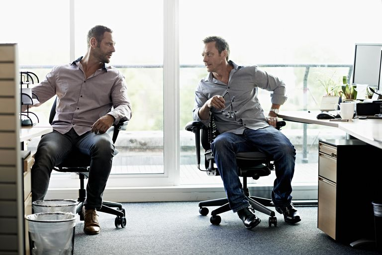 men in office wearing jeans and talking