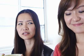 annoyed woman looking at another smiling woman