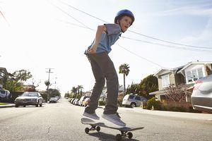 Boy skateboarding on road