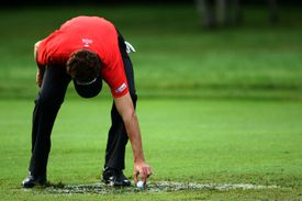 Michael Letzig pulls his ball out of a mud puddle on the second fairway during round three of the RBC Canadian Open at Glen Abbey Golf Club on July 26, 2009 in Oakville, Ontario, Canada