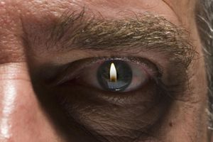 Flame projected in eye of senior man, close-up