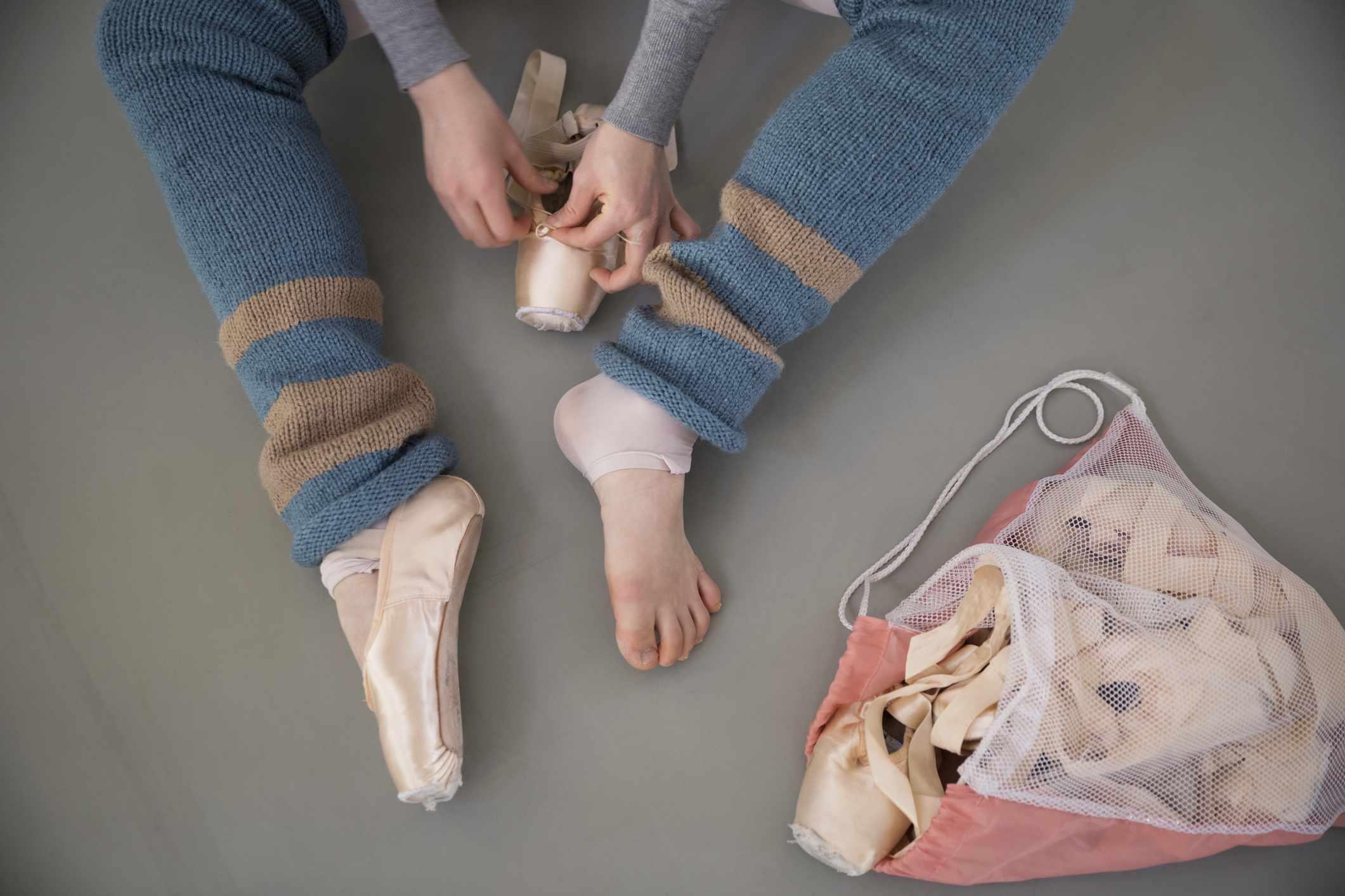 female ballet dancer in leg warmers putting on ballet shoes