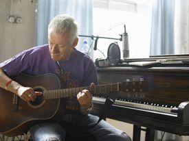 mature man playing guitar