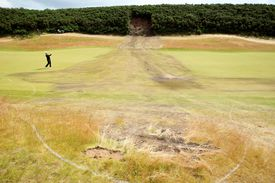 Peter Hanson of Sweden hits an approach shot next to ground under repair, following a landslide on the 1st hole during the final round of The Barclays Scottish Open at Castle Stuart Golf Links on July 10, 2011