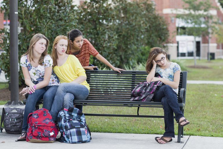 group of girls bullying another girl on a bench