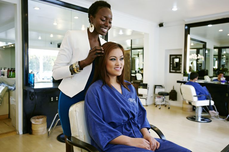 Woman having hair done by owner of salon
