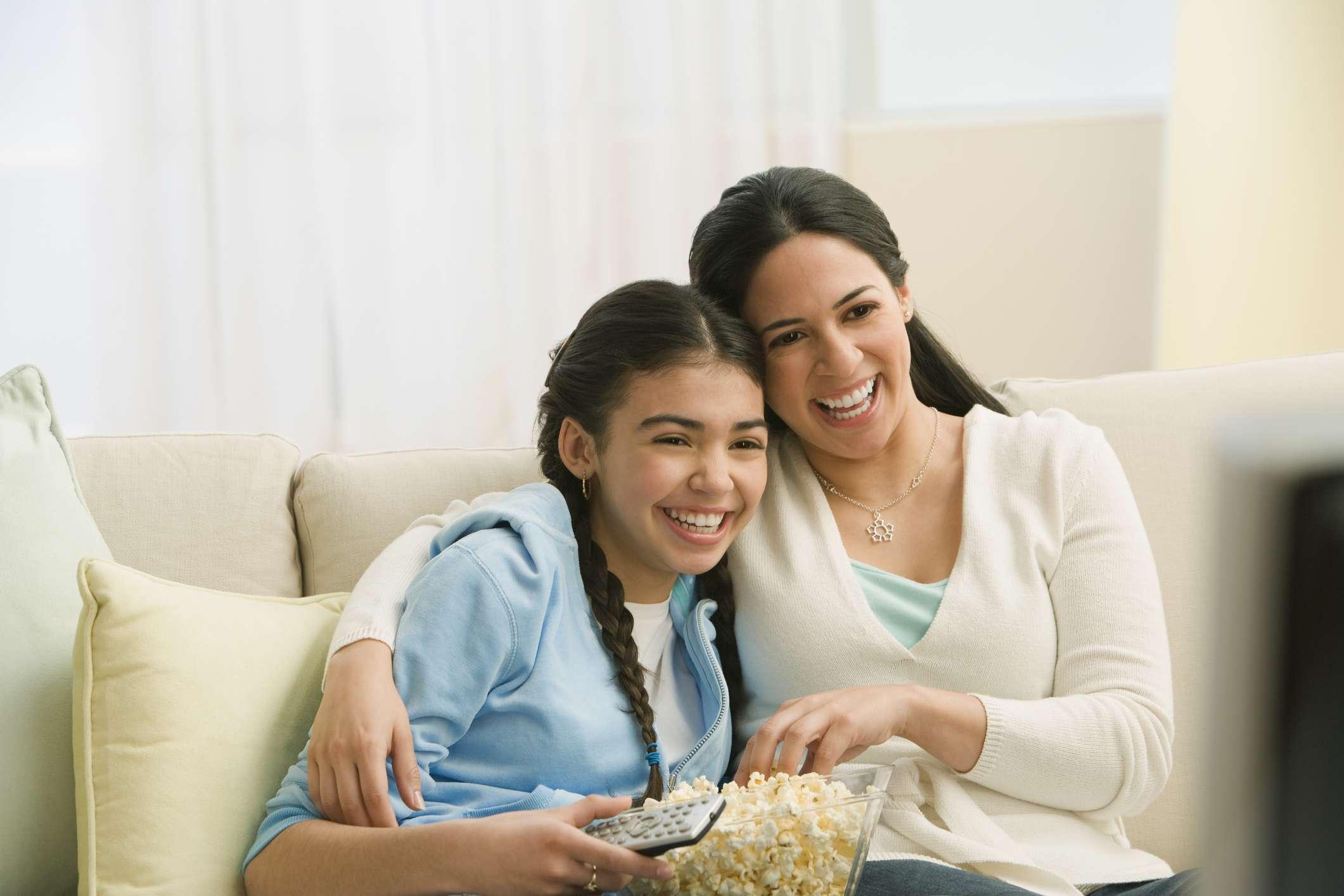 Hispanic mother and daughter watching movie