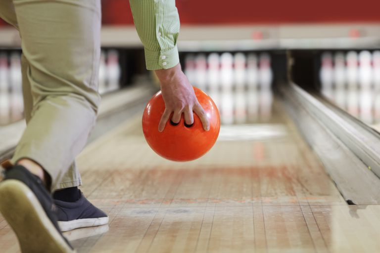 Man about to bowl orange bowling ball