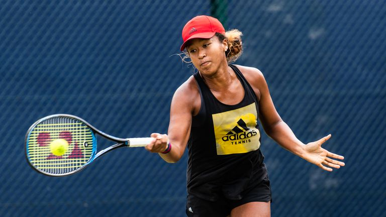 Naomi Osaka uses a forehand tennis swing on the court.