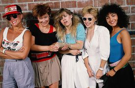 Publicity photo of the Go-Go's standing in front of a brick wall.