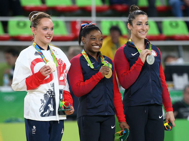 Three gymnasts holding medals