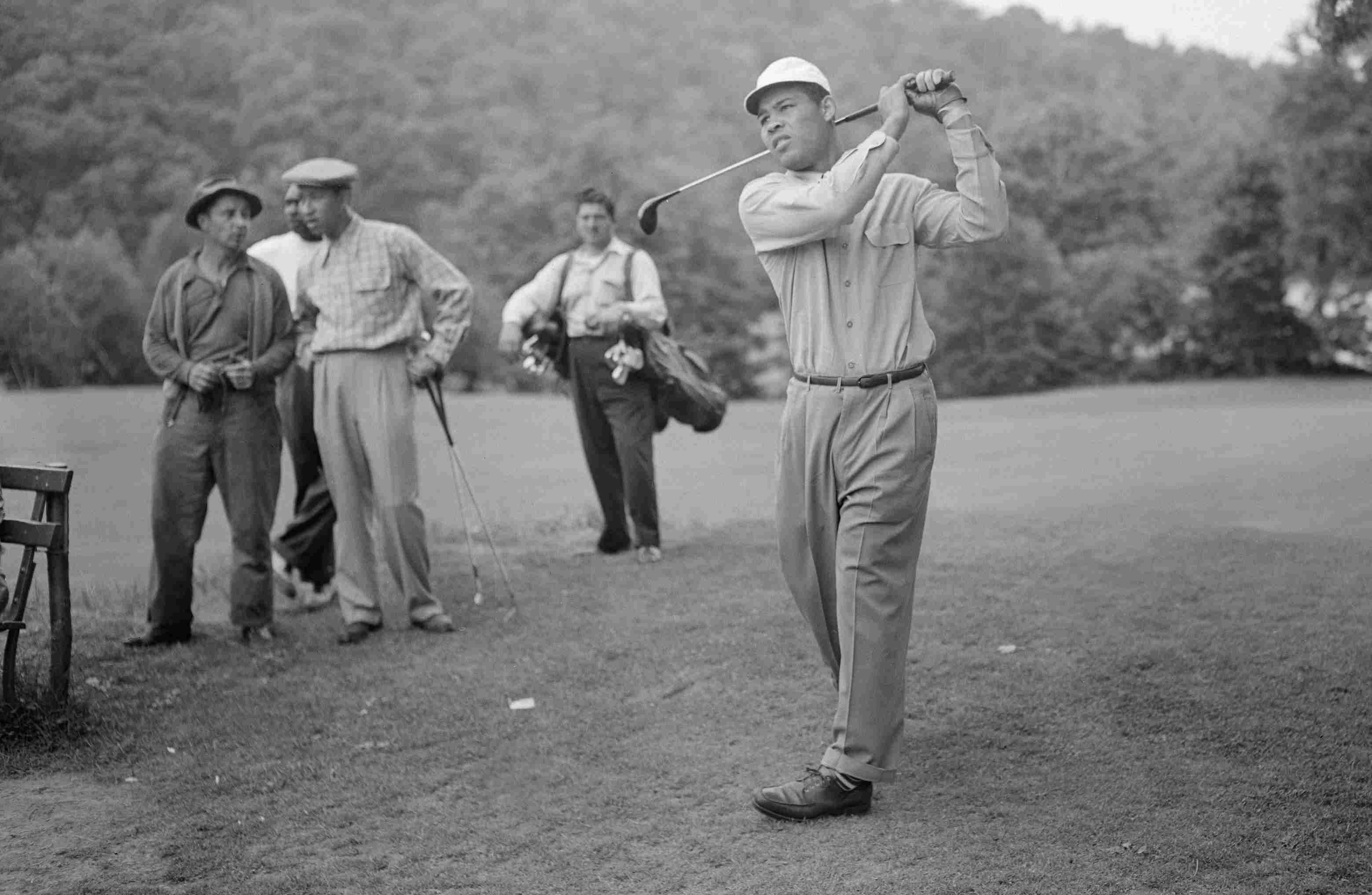 Boxing legend Joe Louis tees off at a golf course in Yonkers, N.Y., in 1946.