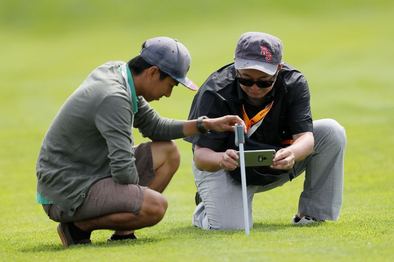 Members of a television crew measure the primary rough at a golf course
