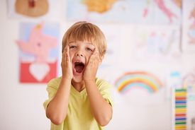 A young boy cupping his face while screaming