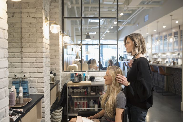 hair stylist and client looking in mirror at salon