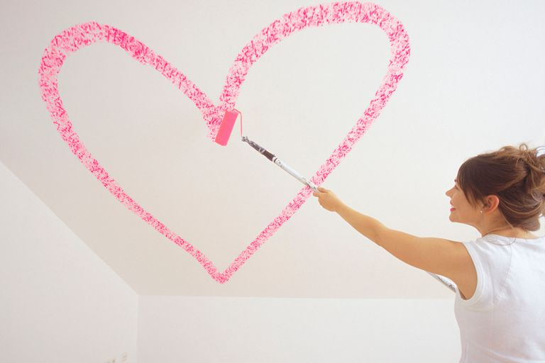 A woman painting a large pink heart on a wall