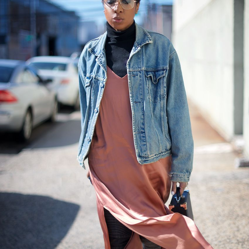 Woman wearing a long dress with a turtleneck and denim jacket