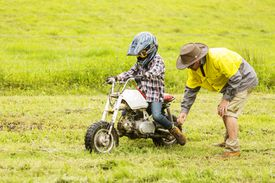 Man helping child learn to ride motorcycle.