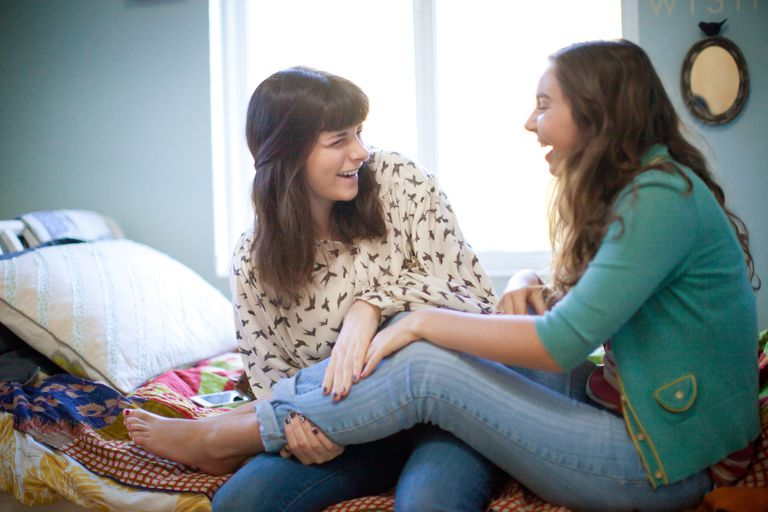 Two teenage girls laugh together in bedroom