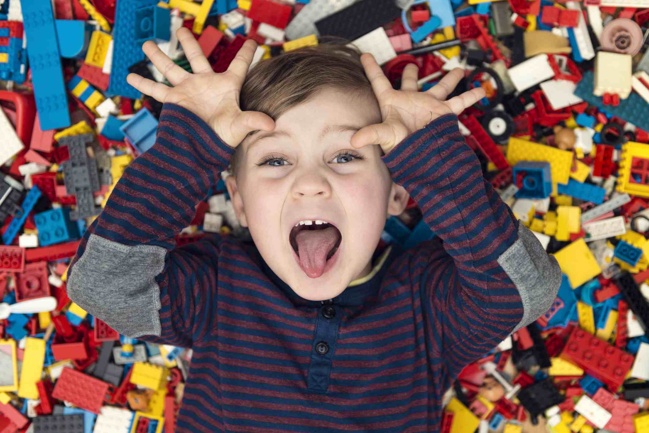 Boy laying on a pile of legos