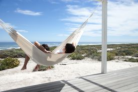 A couple relaxes in a hammock.