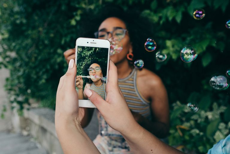 woman taking photo of friend blowing bubbles on iphone